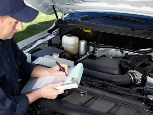 technician with clipboard inspecting a car